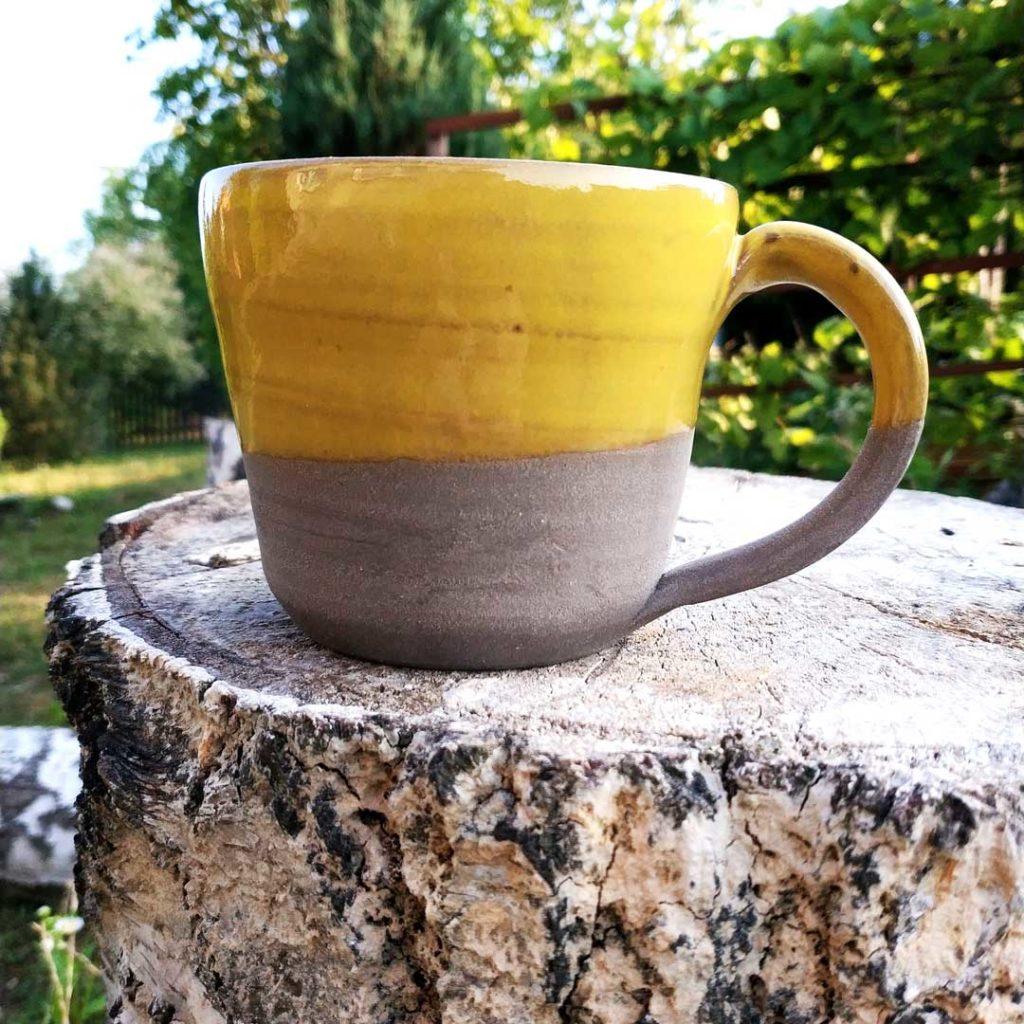 Ceramiczny kubek, w kolorze zółtym. Dostępny na kiermaszu rękodzieła.